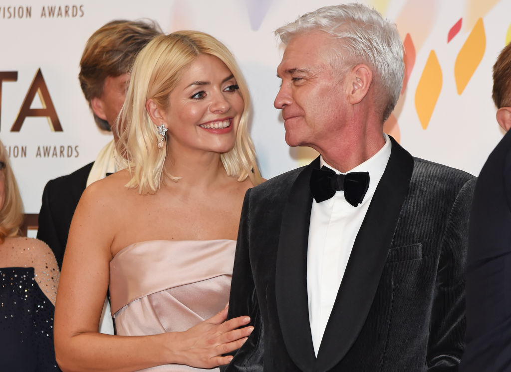 Holly Willoughby and Phillip Schofield look at each other and smile on the red carpet at the National Television Awards.