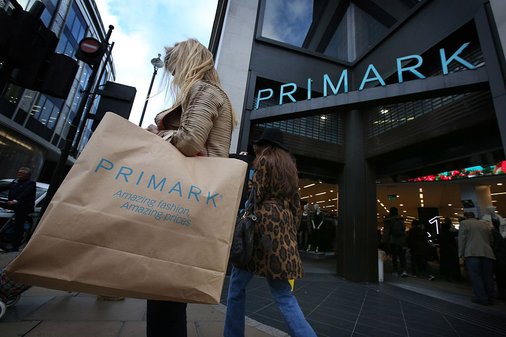 A woman leaves a Primark store with her child, carry a paper Primark bag with her purchases
