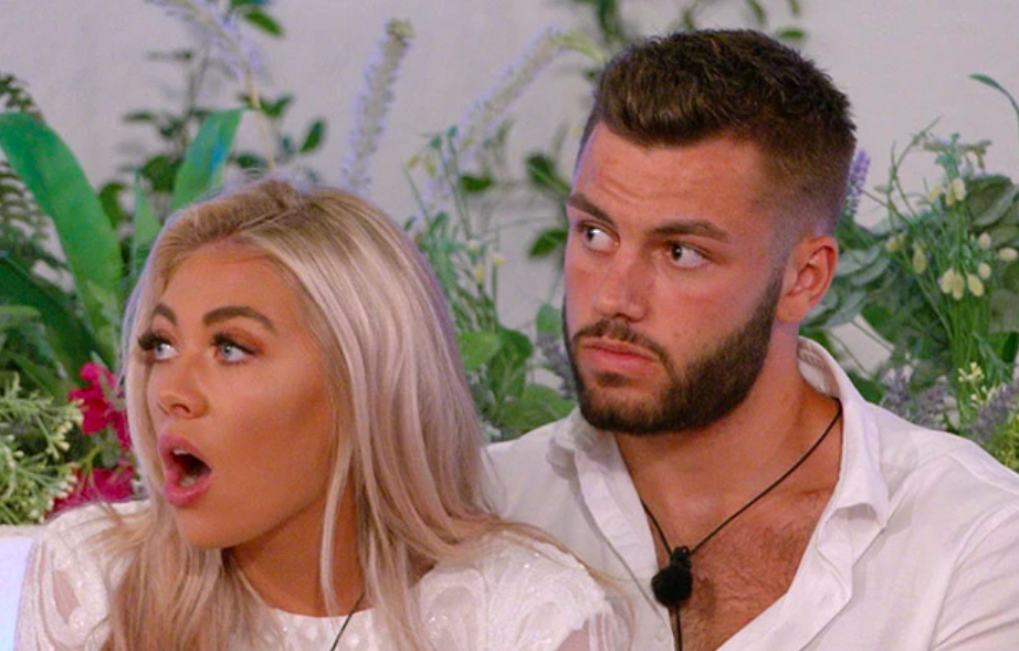 A scene from the most recent series of Love Island, featuring winners Paige Turley and Finn Tapp