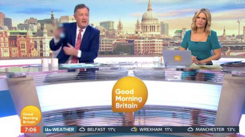 Piers Morgan holding up his phone, showing the image in question. We have blurred the image itself out.
