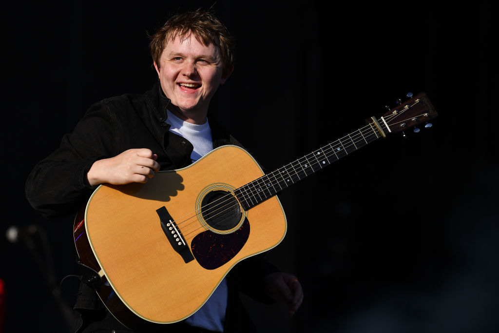 Lewis Capaldi on stage at his concert, holding his guitar